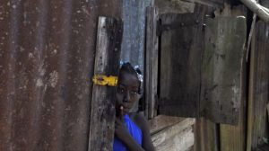 In this Sept. 30, 2013 photo, Maria Julia Deguis, 10, looks out from her home in Los Jovillos village, known as a batey, in the Monte Plata province of the Dominican Republic. Maria, like with her mother and brother, is of Haitian descent and was born in the D.R., but she may lose her citizenship, and the rights that go along with it, because of a recent Constitutional Court decision. (AP Photo/Manuel Diaz) (THE ASSOCIATED PRESS)